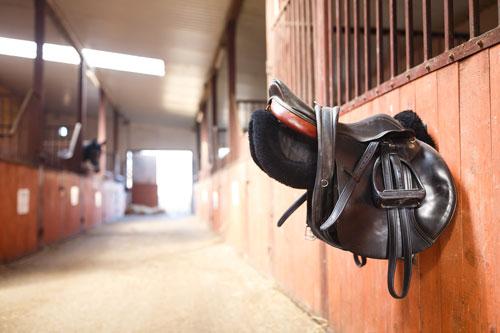 Sattel hängt an einem Pferdestall als Beispielbild